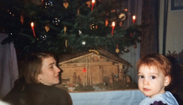 My sister shows my then-tiny daughter the nativity scene and tree