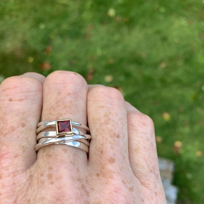 a princess cut garnet is set in 18k yellow gold on top of a wrapped, hand-forged sterling silver ring